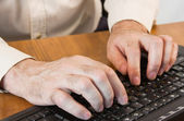 Masculine hands working on a keyboard — Stockfoto