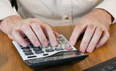 Masculine hands working on a calculator — Stock Photo