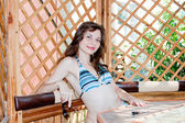 Woman in a swimming suit sits in an arbour — Stock Photo