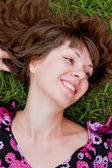 Woman lies on a green grass — Stock Photo