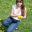 Woman in a park on a walk with dandelions in hands — Stock Photo