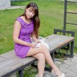 A young beautiful woman sits in a park on a bench — Stok fotoğraf