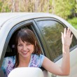 Woman a driver after the helm of car waves a hand — Stock Photo