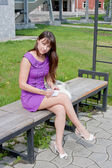 A young beautiful woman sits in a park on a bench — Stock Photo