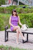 красивая женщина сидит в парке на лавочке — Стоковое фото