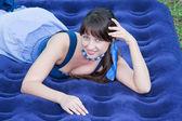 Mulher bonita na natureza encontra-se em um colchão inflável — Fotografia Stock