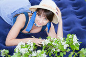 A young beautiful woman in a hat lies with the sprigs of floweri — Stock Photo