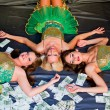 Three young beautiful women lie on money — Stock Photo #13989616