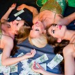 Three young beautiful women lie on money — Stock Photo #13989642