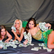 Three young beautiful women lie on money — Stock Photo #13989690