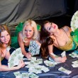 Three young beautiful women lie on money — Stock Photo #13989760