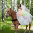Young woman in the dress of fiancee on a horse — Stock Photo #14049554