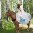 Young woman in the dress of fiancee on a horse — Stock Photo