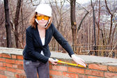 Business woman in a helmet and goggles with tape measure in hand — Stock Photo