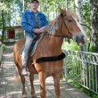 Stock Photo: Msits astride on horse