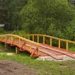 New wooden bridge in field — Stock Photo