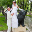 Happy groom and fiancee in a park near the sculpture of dog — Stock fotografie