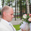 Groom looks over wedding nosegay attentively — Stock Photo #14105713