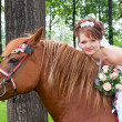 Stock Photo: Happy fiancee sits astride on horse