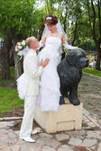 Happy groom and fiancee in a park near the sculpture of dog — Stock Photo