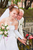 A happy groom and fiancee in a park hang a lock on the bridge of — Stock Photo