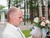 A groom looks over a wedding nosegay attentively — Stock Photo