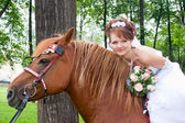 Happy fiancee sits astride on a horse — Stock Photo