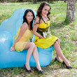 Two young beautiful women on nature by a canicular sunny day — Stock Photo