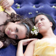 Two young beautiful women lie on an inflatable mattress on natu — Stock Photo #17373543