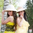 Two young beautiful women in hats on nature in a park — Stock Photo #17373565
