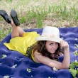 A young beautiful woman lies on an inflatable mattress on nature in a park — Stock Photo