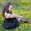 Young woman on the flowering lawn of dandelions — Stock Photo