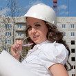 Young  woman in a helmet and by documents in hands — Stock Photo