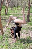 Une jeune femme se livre à une gymnastique dans un parc d'été — Photo