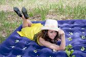 Une belle jeune femme se trouve sur un matelas gonflable sur la nature dans un parc — Photo