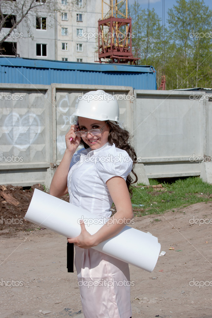 Young  woman in a helmet and by documents in hands on a background building — Stock Photo #17375459