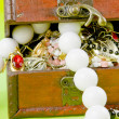 Foto Stock: Small box with treasures on light green background