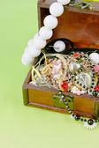 Small box with treasures on a light green background — Stock Photo