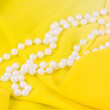 Beads from white pearls on yellow fabric — Stock Photo