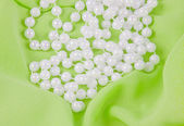Beads from white pearls on green fabric — Photo