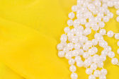 Beads from white pearls on yellow fabric — Photo