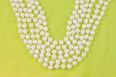 бусы из белого жемчуга на зеленой ткани — Стоковое фото