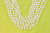Perles de perles blanches sur le tissu vert — Photo