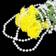 Yellow chrysanthemums and beads are pearls on a black background — Stock Photo #18407305