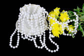 Yellow chrysanthemums and beads are pearls on a black background — Stock Photo