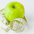 图库照片: Green apple and centimetre on white background