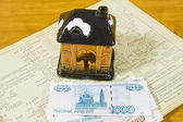 Toy house and Russian money on project documentation — Stock Photo