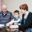 Stock Photo: A grandmother, grand-dad, play with a grandchild in a designer