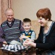 Stock Photo: A grandmother, grand-dad, play with a grandchild in checkers