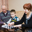 A grandmother, grand-dad, play with a grandchild in checkers — Stock Photo #25830603
